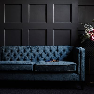 Pippa Jameson Styling. Blue velvet sofa against dark grey panelled walls. Photo Jo Henderson