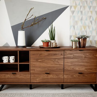 London based Interior Stylist, Pippa Jameson, Styling for Next. Geo walls with a wooden sideboard and brass accessories. Photo Jo Henderson